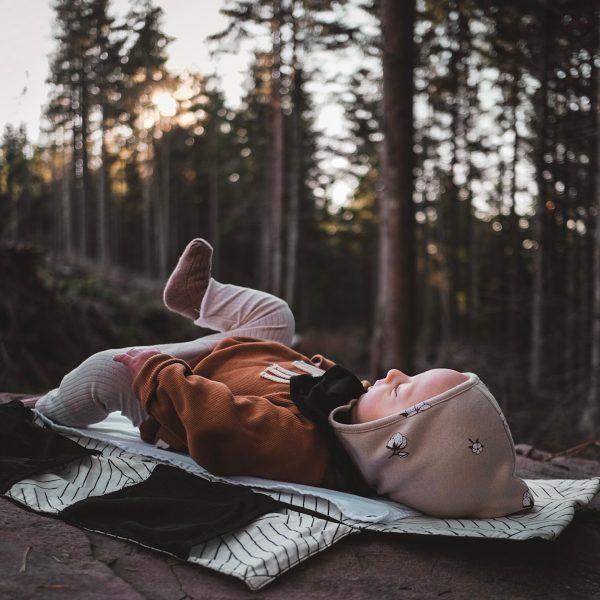 Bébé sur matelas à langer dans foret.